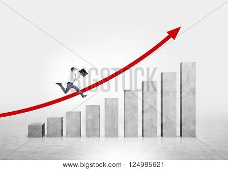 Businessman running up stairs made of concrete blocks. Red arrow up at concrete background. Concept of career growth.