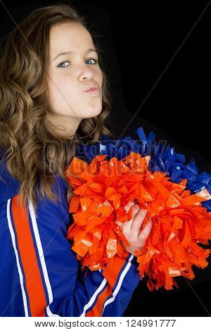 Cute high school cheerleader playfully puckering her lips kissing