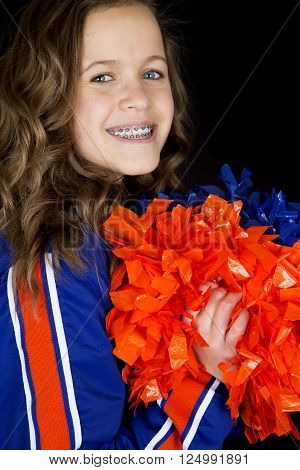 Cute high school cheerleader portrait smiling holding orange pom poms