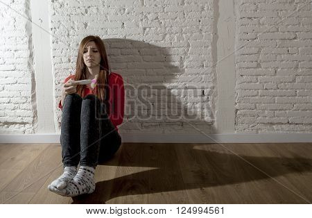 sad and worried pregnant teenager girl or young desperate woman holding positive pink pregnancy test looking scared and devastated at home floor in unwanted baby and unexpected motherhood poster