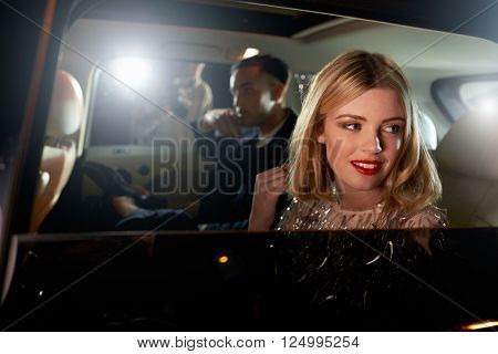 Celebrity couple in back of a car, photographed by paparazzi