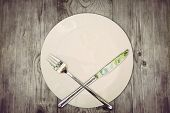 Stop eat concept. Wooden table with empty plate and crossed silver cutlery symbolizing to refuse food. Still life symbolize dieting or unhealthy eating. poster