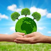 Green planet with trees in hands. Earth day concept. poster