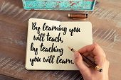 Retro effect and toned image of a woman hand writing on a notebook. Handwritten quote By learning you will teach, by teaching you will learn.  as inspirational concept image poster