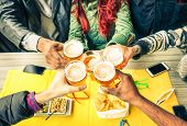 Group of friends cheers with beer cafe interior scene - Multiracial hands holding glasses of Pils in a toast to friendship and happiness -Teenager students gathering in restaurant - Focus on glasses poster