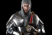 Portrait of Medieval Dirty Face Warrior with chain mail armour and red cross on sword. Dark Background poster