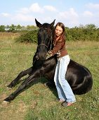 teenager and her friend black stallion sitting in a field poster