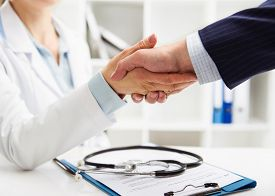 Woman doctor and businessman shaking hands in medical office