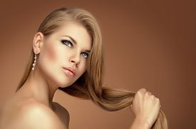 Handsome elegant model wearing jewelery touching her long healthy hair. Beautiful young Caucasian woman with professional make up and hairstyle posing in studio.