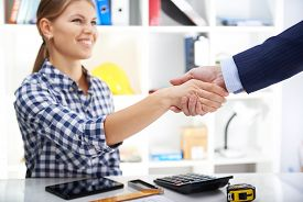 Partnership and investment concept. Cheerful female designer shaking hands with customer over table with construction instruments, calculator and digital tablet.