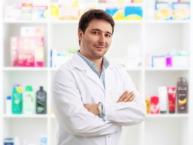 Young cheerful pharmacist chemist standing in retail drug store. Handsome male doctor wearing uniform selling drugs.