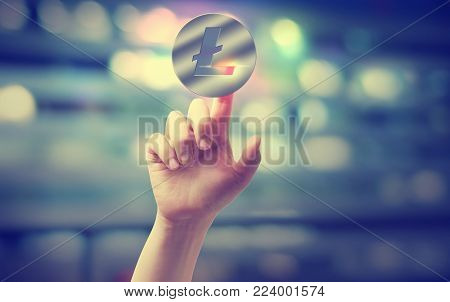 Litecoin with hand pressing a button on blurred abstract background