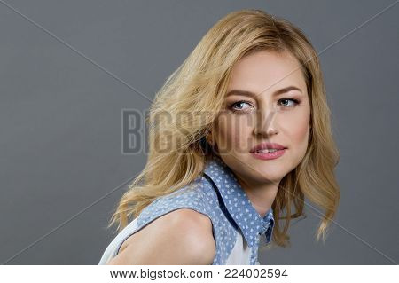 Close-up studio portrait of a beautiful middle aged blonde woman. Gray backgroundClose-up studio portrait of a beautiful middle aged blonde woman. Gray background, copy space