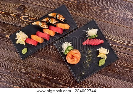 Two plates of nigiri sushi top view. Plates of cooked and uncooked nigiri sushi. Concept, sushi cooking, before and after.