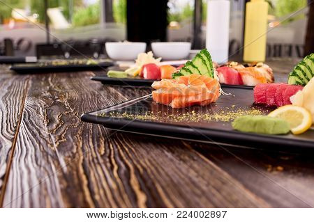 Perspective view on table with sushi. Juicy fresh sushi with salmon, tuna and eel, perspective view.