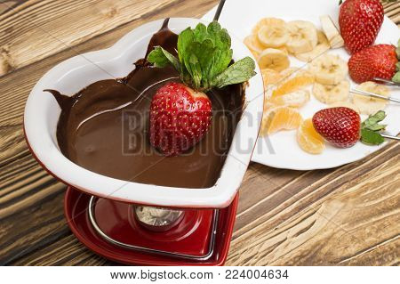 Chocolate fondue with strawberries and fruits served in a restaurant. Valentine's Day.