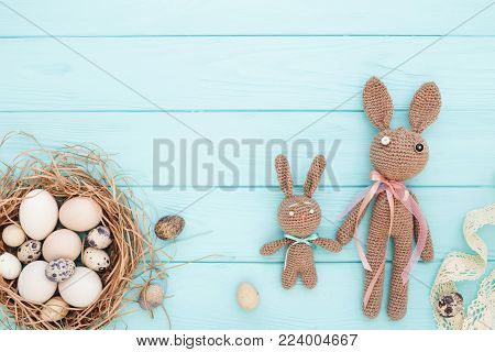 Easter flat lay with eggs in nest and homemade Easter bunnies on blue wooden background. Top view.