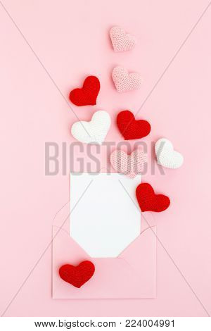 Happy Valentine's Day card in envelope with pink, white & red spreading hearts on pink background. Holiday Congratulation. Romantic Love message. Flat lay, vertical.