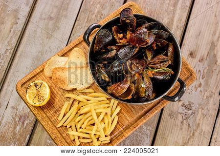 Many mussels in saucepan and side dish. Top view saucepan with mussels and side dish on board.