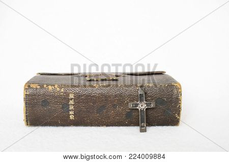 Single Antique Leather Bible with Small Cross made of Wood Metal and Nails on White Background