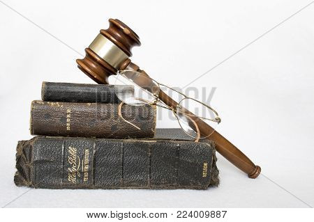 Stack of Three Old Leather Bibles with Rimless Glasses and Wooden Gavel on White Background