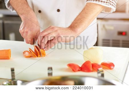 Cooker man slicing carrot using knife. Chef hands using knife. Slicing action. poster