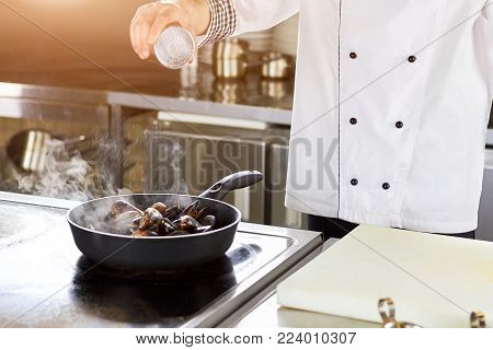 Chef salting dish with steamed-mussels. Mussels dish cooking.