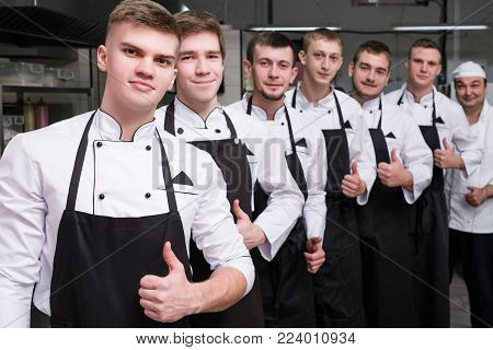Contestants of a tv cooking talent show stand in a row ready to show their skills in the competition. Only one can be a winner