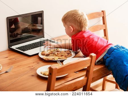 Children, technology and home concept  - little boy child eating meal while using laptop pc computer at home. Bad habits