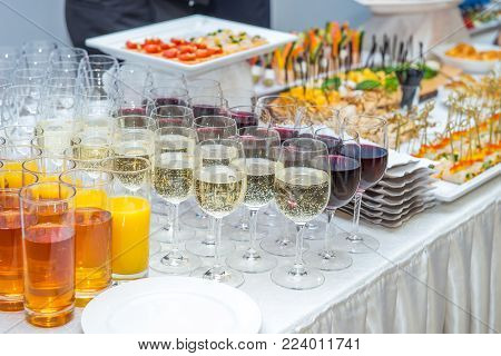 Catering table with alcoholic and non-alcoholic drinks, dishes and snacks food on the event. Service at business meeting, party, weddings. Selective focus, space for text
