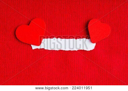 Piece scrap of white paper blank copy space and hearts symbols of love on red fabric textile material background. Valentines day.