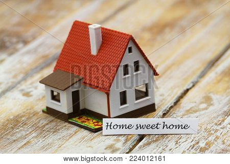 Home sweet home card with miniature model of a house