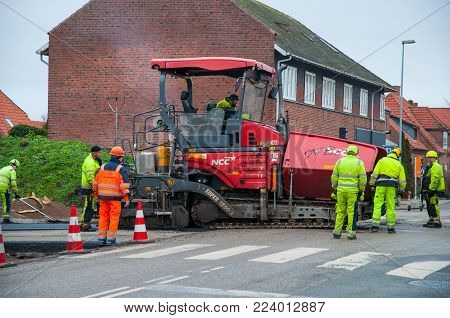 Vordingborg Denmark - January 19. 2018: Paver Laying Asphalt On A New Road With Workers Helping
