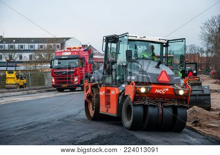 Vordingborg Denmark - January 19. 2018: Road Roller compacting tarmac asphalt on a new road in Denmark