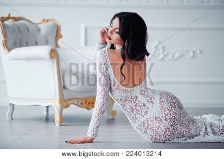 Perfect, sexy legs and ass of young woman wearing seductive white dress posing near luxury vintage chair.