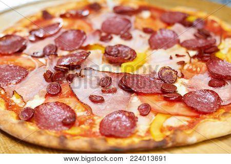 Freshly baked juicy salami pizza. Close up baked salami pizza.
