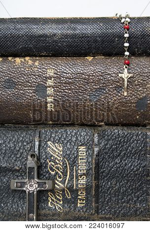 Background of Stacked Antique Leather Bibles with Antique Cross of Wood Metal and Nails and Antique Rosary