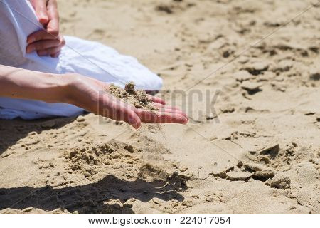 Woman's hand touching sand at the shore of the sea - concept of native place. Woman holds her hand over the sand on the beach - concept of vacations and tourism. Sand on the hand.