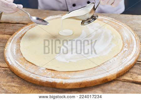 Pouring sauce from sauce boat to pizza crust. Process of pouring creamy sauce.