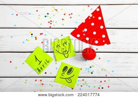 Clown nose, party cap and notes with funny faces on wooden background. April fool's day celebration