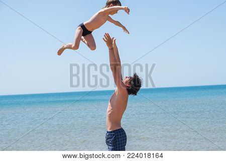 Young happy father holding up in his arms little son putting him up at the beach, having fun with the kid.