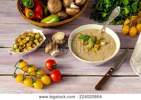 Fresh, vegetarian, mushroom soup puree in a bowl, crouton and vegetables in a wicker basket on a wooden table close-up.