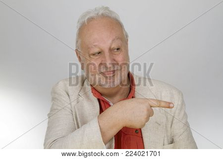 Senior pointing with finger - on bright background