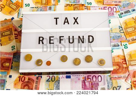 Text  Tax Refund written on lightbox surrounded with Euro Banknotes