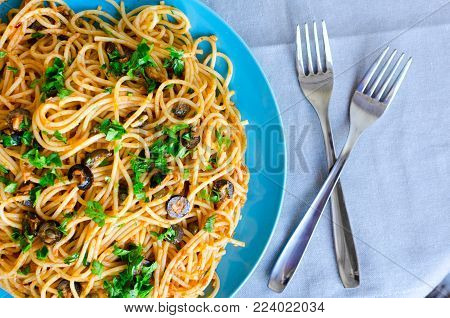 Spaghetti Alla Puttanesca - traditional italian pasta with black olives, tuna, anchovies, capers and parsley. Vegetarian food. Italian cuisine. Top view.