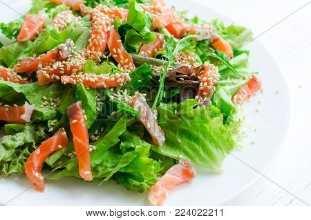 Leaf vegetable salad with green salad mix, arugula, smoked salmon and sesame seeds on white plate. Healthy eating concept.