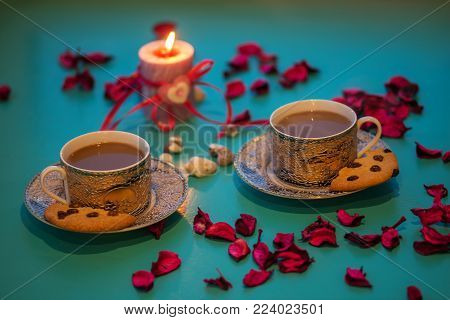 Valentine's Day, romantic dinner - two vintage cups of coffee and cookies are standing on a green surface with pink rose petals next to  burning candle with a heart symbol, blurred background.