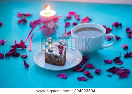 Valentine's Day, romantic dinner for your favorite - big cup of coffee and cake in a heart shape stand on a green surface with pink rose petals next to burning candle.