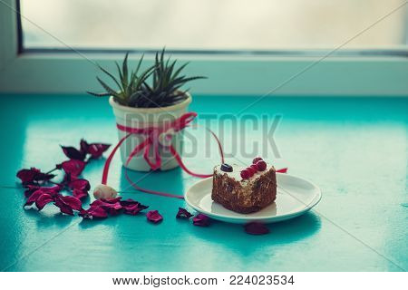Valentine's Day, the day begins with a good mood - a heart shaped cake, stands on a green surface with pink rose petals, next to a cactus with a symbol heart on window blurred background.