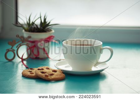 Valentine's Day, breakfast for your favorite - big steaming cup of coffee with a cookies stands on a green surface, next to a cactus and a bicycle symbol with a heart on the background of window.